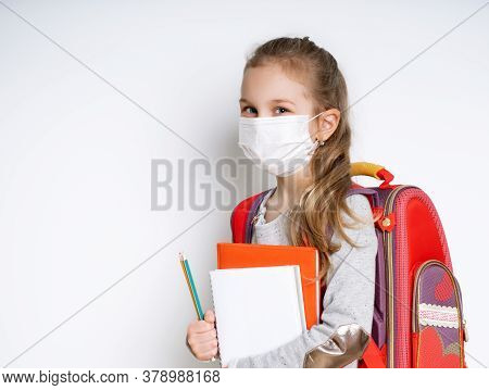 Blonde Little Girl In Gray Jumper, With Colorful Briefcase. Holding Notebooks And Two Pencils. She I