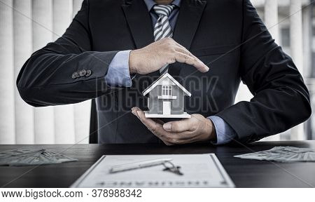 Sales manager or real estate agent prepares to hand over the keys and the house together with the in