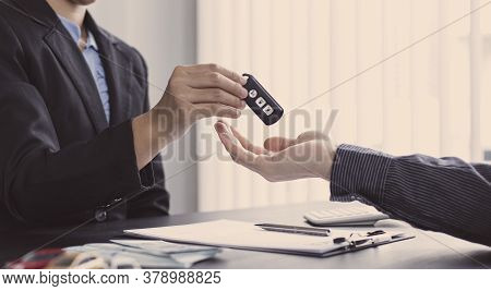 Car sales representative or sales manager submits a car key to a client who has approved financial l