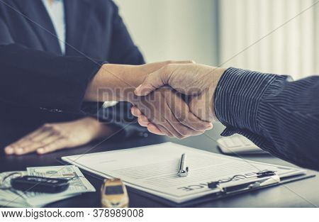 Car dealers or insurance dealers shake hands to congratulate the customers who have signed the car p