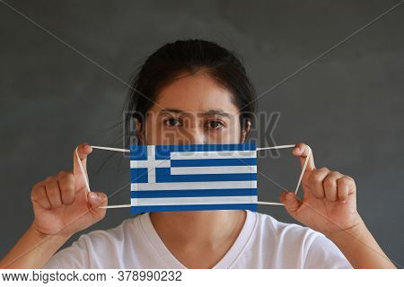 A Woman In White Shirt With Greece Flag On Hygienic Mask In Her Hand And Lifted Up The Front Face On