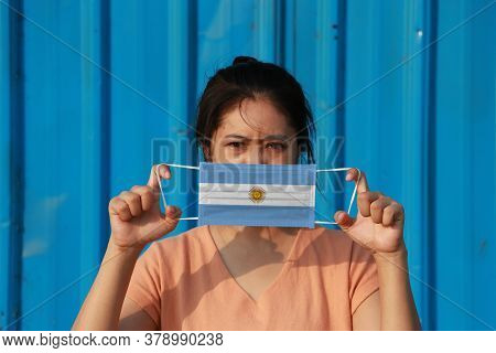 A Woman With Argentina Flag On Hygienic Mask In Her Hand And Lifted Up The Front Face On Blue Backgr