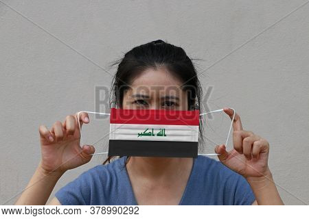 A Woman With Iraq Flag On Hygienic Mask In Her Hand And Lifted Up The Front Face On Beige Color Back