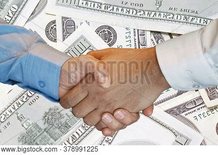 Handshake Of Two Hands Men Closeup On Background Hundred Dollar Banknotes. Handshake Over 100 Dollar