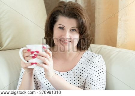 Smiling Woman With A White Cup In Her Hands