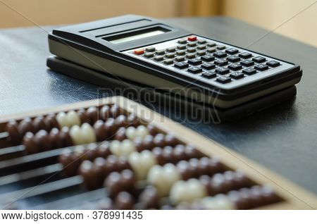 Close-up Old Wooden Abacus And A Calculator On A Black Table. An Obsolete Device For Mathematical Ca