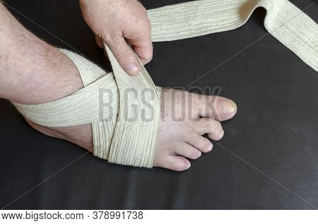 Middle-aged Caucasian Man Produces An Independent Bandage Of His Dislocated Leg. He Puts An Elastic
