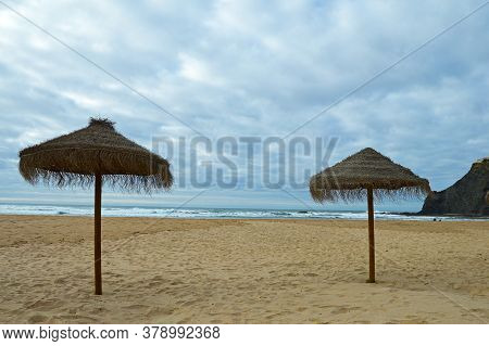 Two Sunshade On The Beach In Odeceixe On The Atlantic Coast Of Portugal