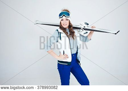 Smiling Girl Skier In A Hat And Mask For Skiing. A Young Woman In Clothes For Skiing And Outdoor Act