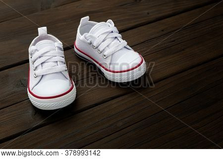White baby sneakers on wooden background