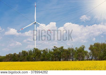 Big Wind Turbine Standing On A Field Of Blooming Canola, The Concept Of Clean Energy, Against The Sk