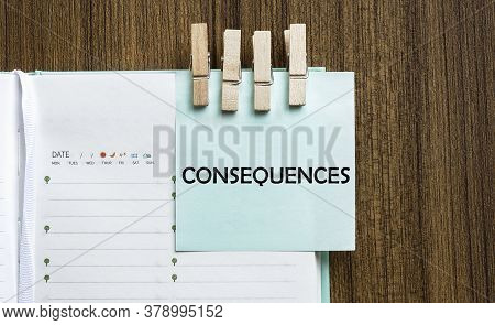 Consequences Notes Paper And A Clothes Pegs On Wooden Background