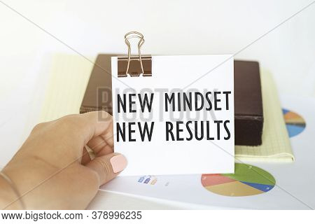 Woman S Hand Holds A Piece Of Paper With Text New Mindset New Results On The Background Of Graphs An