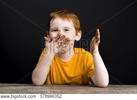 Boy Smeared In Milk Chocolate After Nibbling And Biting Real Cocoa Chocolate In A Bar, Close-up Port