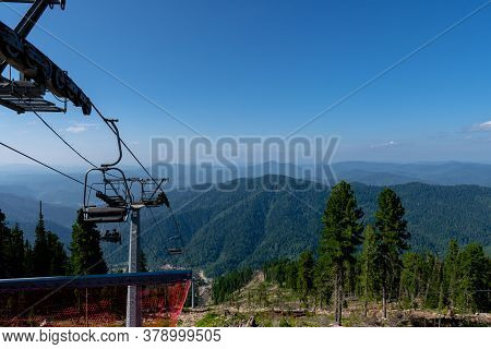 Cable Car Chair Lift In The Mountains. Climbing The Mountain On A Lift. View From The Top Of The Mou