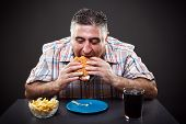 Portrait of a greedy fat man eating burger on gray background poster