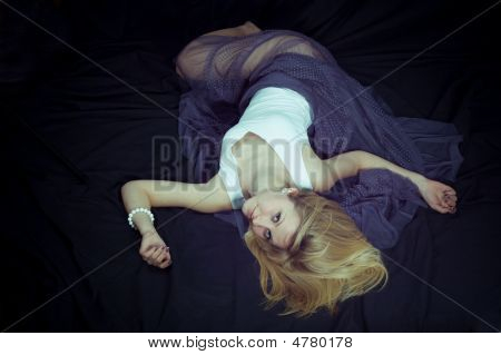 Portrait of a young blonde girl in the black poster