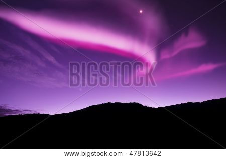 Amazing northern lights over trees and mountains