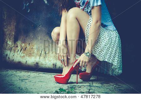 woman legs in red high heel shoes and short skirt outdoor shot against old metal door