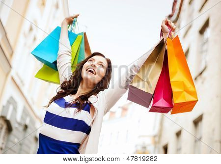 shopping and tourism concept - beautiful woman with shopping bags in ctiy poster