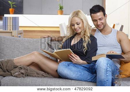 Young loving couple reading book on sofa at home, hugging.
