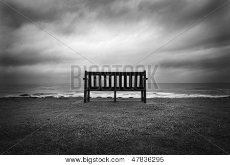 Lonely Bench facing the ocean and dramatic sky poster