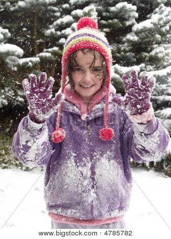 young girl holding hands up while out playing in the snow poster