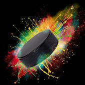 Colorful paint splashing with hockey puckl isolated on black poster