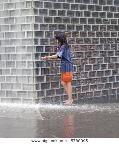 Young girl playing in water fountain