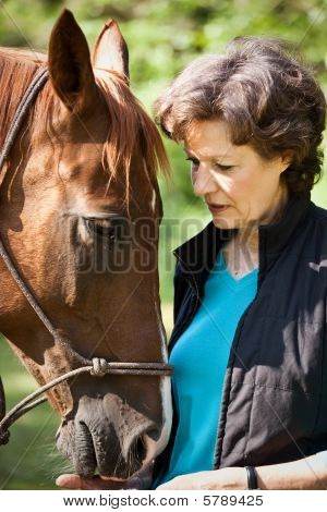 A shot of a senior caucasian woman with her horse poster