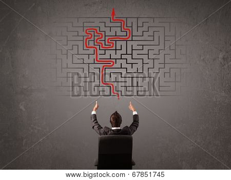 Business man looking at a maze and the way out on brown wall poster