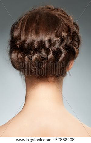 Woman with brunette hair and braid hairdo. Rear view, hairstyle with tress