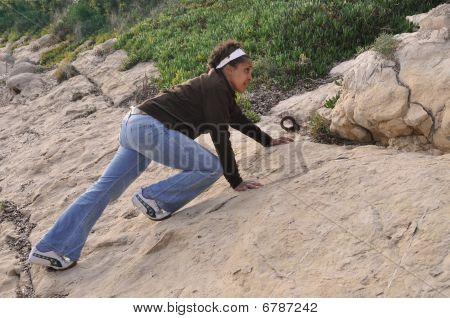 African American professional woman climbing rocks