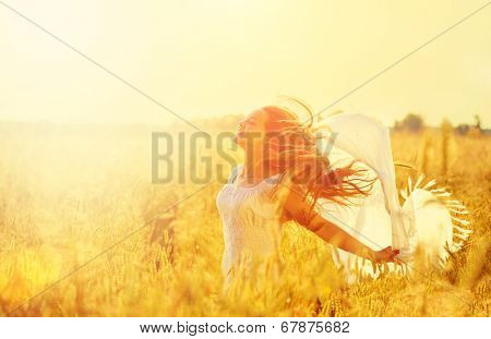 Beauty Girl Outdoors enjoying nature. Beautiful Teenage Model girl in white dress running on the Spring Field, Sun Light. Glow Sun. Free Happy Woman. Toned in warm colors