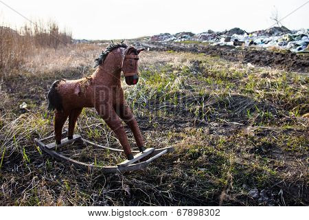 Old threadbare rocking horse thrown away to the dump in the field poster