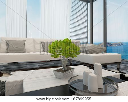 Modern bright airy living room or lounge interior overlooking the sea with large view windows with curtains and blinds, a modern upholstered lounge suite and a bonsai on the table