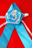 Awareness Ribbon with rose on red background poster
