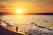 Man walking alone on the beach at sunset. Calm sea with rippling waves. poster