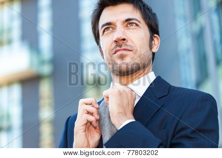 Confident businessman adjusting his necktie