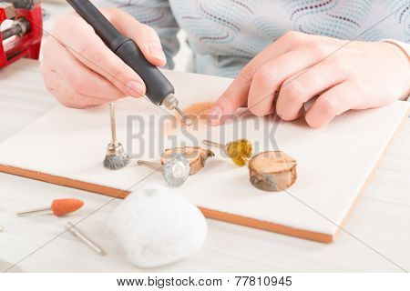 Woman using a high speed rotary multi tool to engrave ornament on the tile