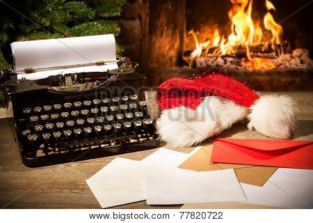 Old typewriter and Santa Claus hat on desk in front of fireplace