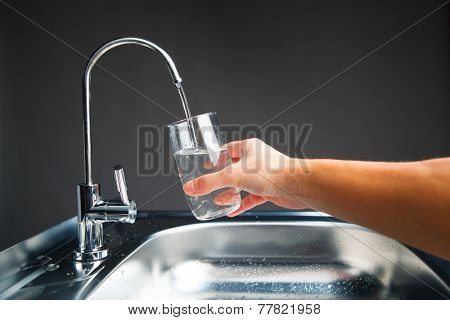 hand pouring a glass of water from filter tap