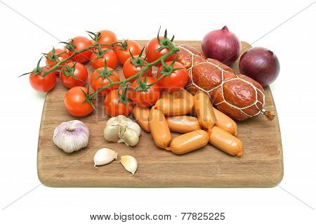 Sausages, Garlic And Cherry Tomatoes On A Cutting Board Isolated On White Background