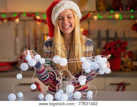 Portrait Of Happy Teenager Girl In Santa Hat Untangling Christma