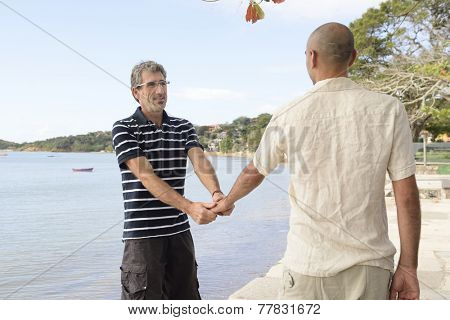 Happy gay couple on vacation holding hands