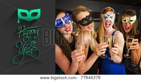 Attractive friends with masks on holding champagne glasses against classy new year greeting