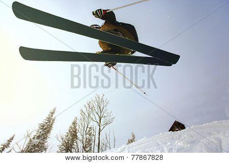 Jumping skier at jump inhigh mountains at sunny day