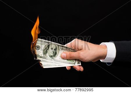 finances, people, savings and bankruptcy concept - close up of male hand holding burning dollar cash money over black background poster