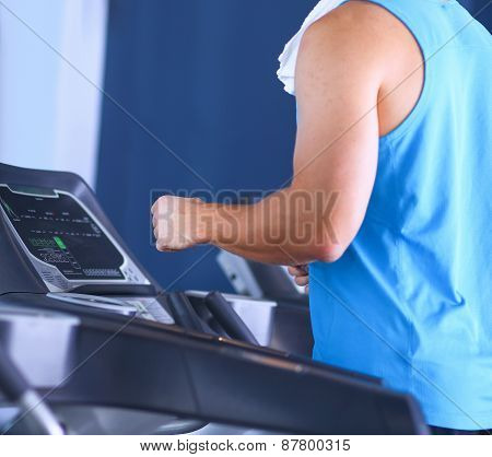 Man at the gym exercising on cross trainers