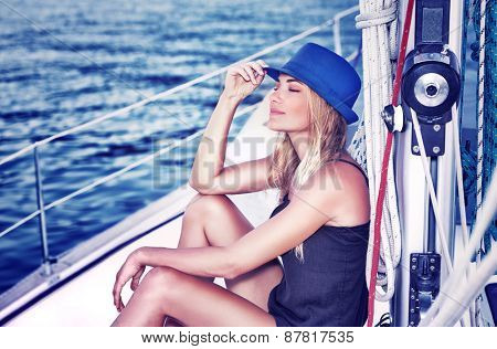 Relaxed girl with closed eyes of pleasure sitting on sailboat, enjoying mild sunlight, fashion model in luxury sea cruise, summer vacation and travel poster